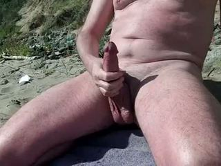 Nag gej prikazuje tič na the nudist plaža