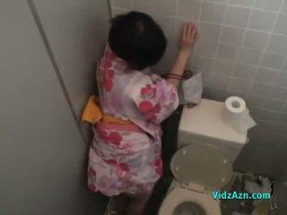 אסייתי נערה ב kimono מזוין מן מאחורי זרע ל תחת ב the toilette